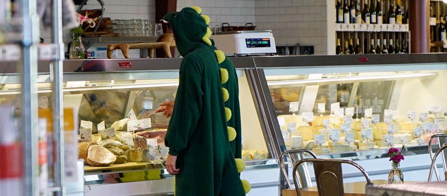 Man in dinosaur onesie at a store